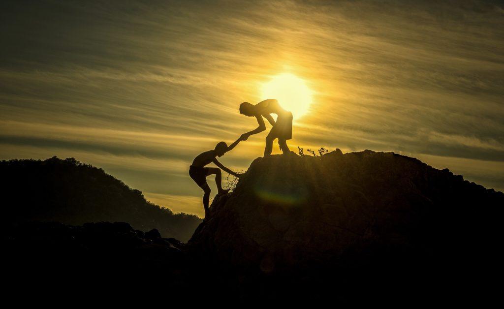 Une personne se fait aider pour gravir une montagne